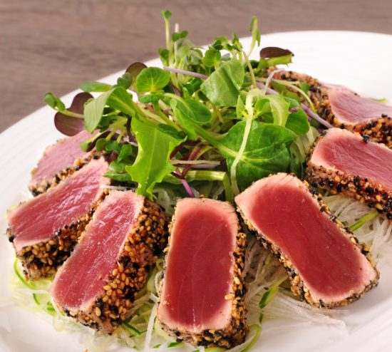 Seared tuna coated sesame seeds with green salad on white plate